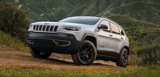 Image of a white 2019 Jeep Cherokee driving up a hill on a dirt road.